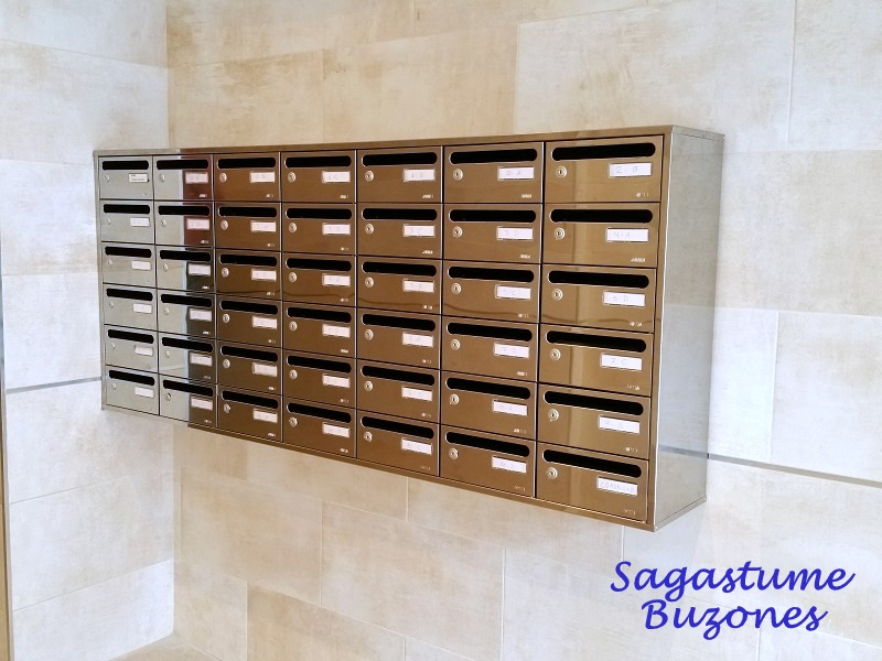 Agrupación de buzones intalados en Santander, fabrica joma. Modelo Interior horizontal con cuerpo negro y puerta de acero inoxidable brillo. Agrupados y con envolvente de 4 piezas en acero inoxidable.