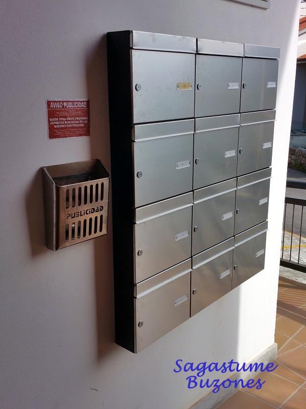 Agrupación de buzones verticales para comunidades instalados en Santander con cuerpo negro y puerta de acero inoxidable satinado. Apertura lateral y tamaño revistero.