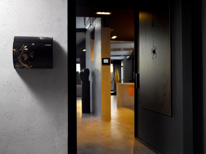 Buzón individual, de exterior Modelo AURA - ARREGUI - Acero pintado en color negro y con dibujo de flor.