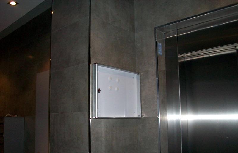 Tablón de anuncios instalado en una comunidad Modelo 12H de BTV, con trasera de acero pintado en color blanco y perfiles de aluminio natural. Puerta de metacrilato transparente con cerradura. Capacidad para dos folios.
