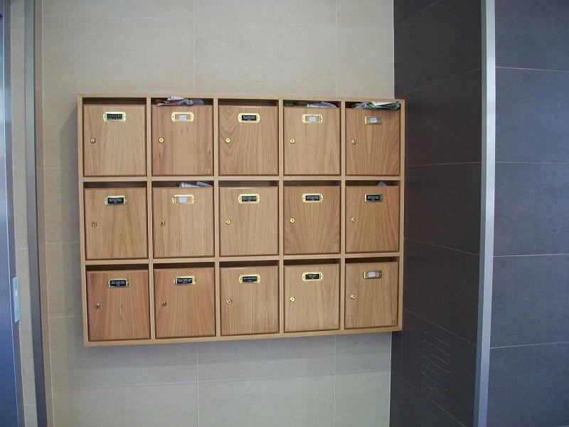 Agrupación de buzones de madera barnizada de Roble, buzones de interior verticales.