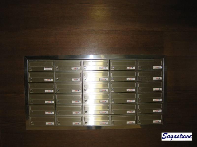 Buzón modelo Kompact (Joma) con puerta de acero inoxidable mate empotrados en la pared y con tapajuntas perimetral a juego.