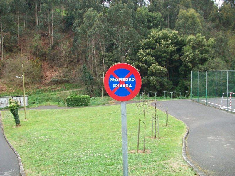 Señal de tráfico prohibido aparcar y estacionar rotulada con vinilo en color blanco de propiedad privada. Fabricada en aluminio con poste para enterrar.