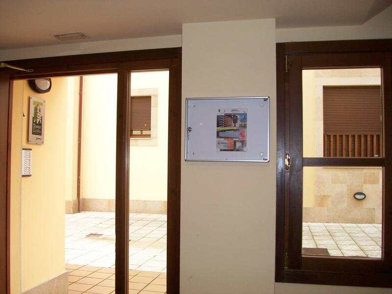 Tablón de anuncios 12H (Btv) de aluminio natural color plata y puerta de metacrilato transparente. Capacidad para 2 folios.
