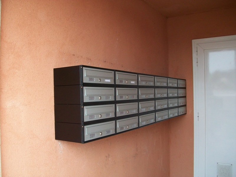 Buzón modelo Tecnum (Arregui) con puerta de aluminio color plata. Buzones colgados de la pared con un envolvente alrededor en color negro.