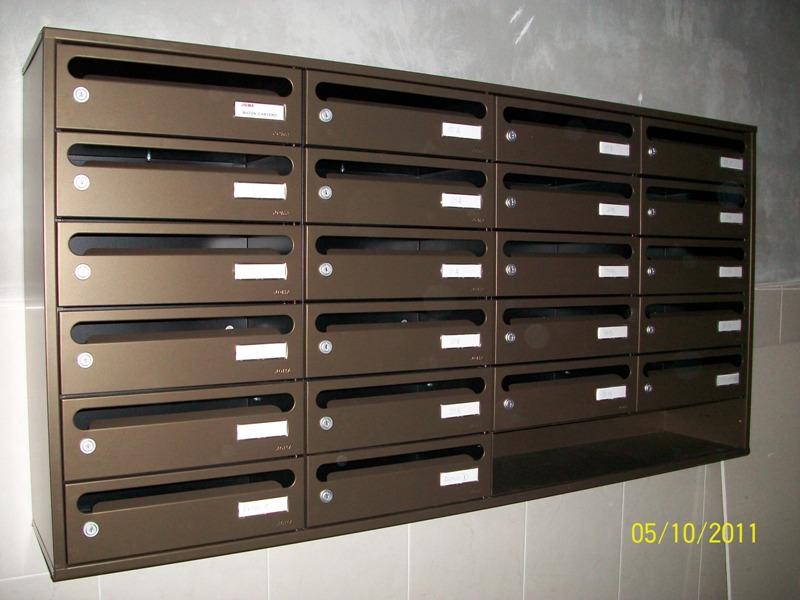 Buzón Modelo Hall-23 (Joma) con cuerpo en color negro y puerta de color bronce meteorite. Tamaño revistero. Apertura lateral. Buzones colgados de la pared con un envolvente de color bronce a juego.