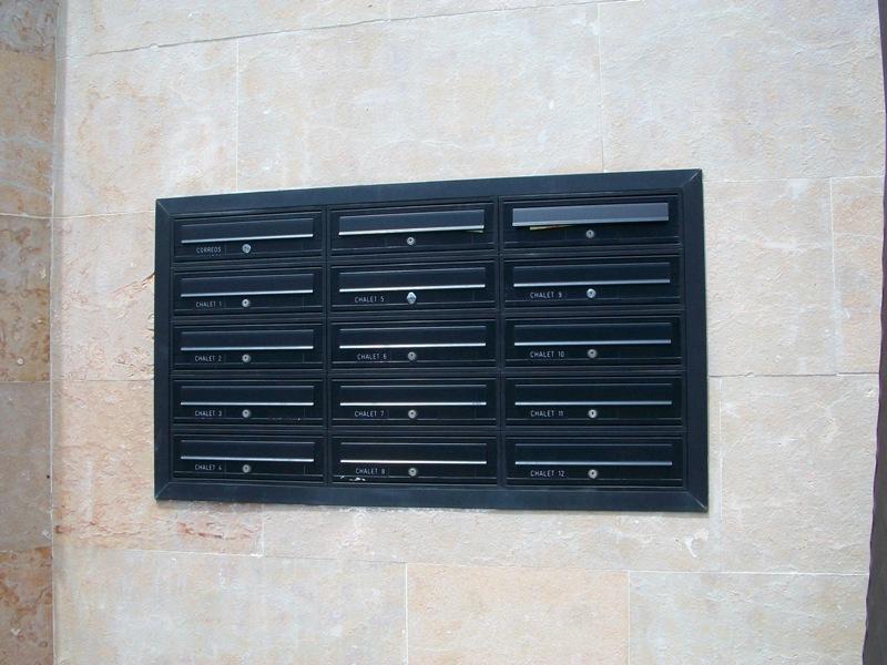 Detalle de buzones modelo Tecnum (Arregui) con puerta de aluminio color negro. Buzones empotrados en la pared con tapajuntas perimetral en color negro.