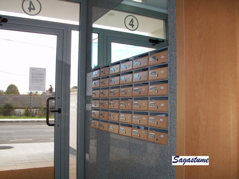 Buzones para comunidades con cuerpo metálico color plata y puerta de madera de roble. Apertura hacia arriba.