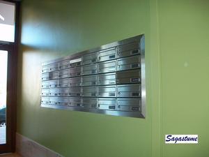 Buzón modelo Kompact (Joma) con puerta de acero inoxidable brillo empotrados en la pared con tapajuntas de acero inoxidable.