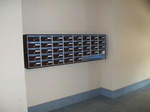 Buzón modelo Lobby (Joma) con cuerpo pintado en color plata y puertas en color marron chocolate. Apertura hacia arriba. Colgados de la pared con un envolvente alrededor.