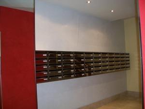 Buzón Modelo Hall-23 (Joma) con cuerpo en color negro y puerta de acero inoxidable brillo. Tamaño revistero. Apertura lateral.